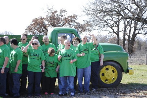 Belinda Stephens poses with the crew in matching green shirts, standing in front of a green farm truck