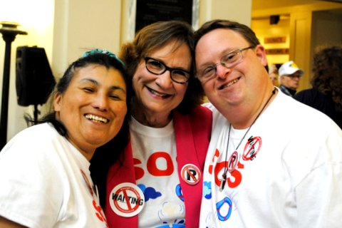 A female and male program member side hug a female volunteer, all smiles